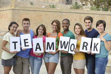 Group of young people holding teamwork sign