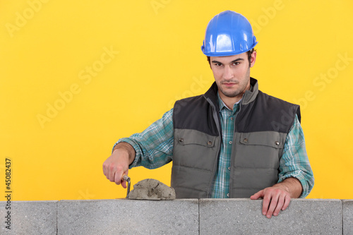 Man with trowel spreading cement on wall