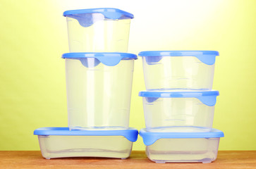 Plastic containers for food on wooden table on green background