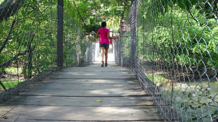 Woman walking over a suspension bridge