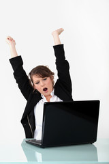 happy woman gesturing in front of laptop computer