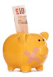 Piggy bank with plaster and ten pound note