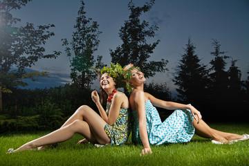 Two smiling girls sitting in a beautiful garden