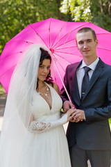 Newly-married couple in a summer garden under a pink umbrella
