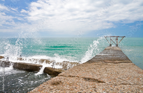 Breaking wave with sparks on the Black Sea coast. Sochi, Russia