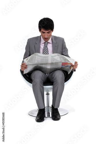Businessman looking in shock at his newspaper