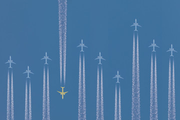 Row of airplanes flying by with one in the other direction