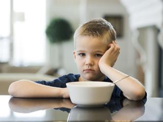 """USA, Utah, Alpine, boy (6-7) resting cheek on hand by bowl"""