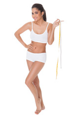 Shapely woman measuring her waist