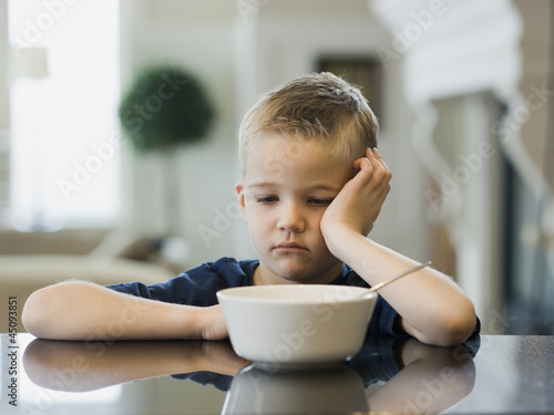 """USA, Utah, Alpine, boy (6-7) resting cheek on hand by bowl"""