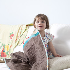 """USA, California, San Francisco, girl (2-3) sitting on sofa covered with blanket"""