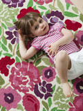 """USA, California, San Francisco, girl (2-3) lying on back on carpet with floral patterns"""