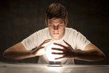 Studio shot of young man with hands around glowing crystal ball