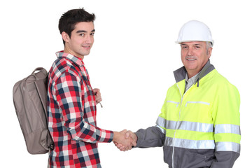young apprentice shaking hands with senior foreman