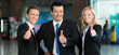 Freundliche, motivierte Business-Gruppe mit Daumen hoch