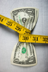 Studio shot of yellow measure tape squeezing two one dollar bills