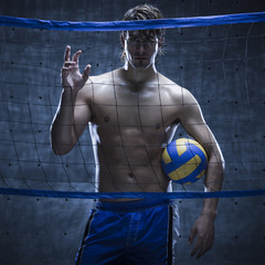 Studio shot of volleyball player standing behind net