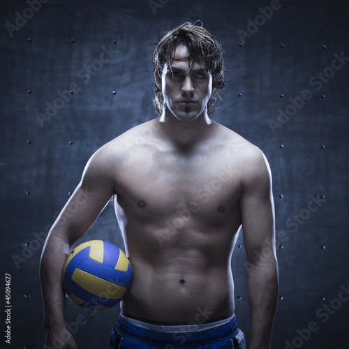 Studio shot of volleyball player standing and holding ball