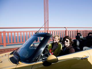 """""""USA, California, San Francisco, young couple passing Golden Gate Bridge in convertible car"""""""