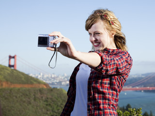 """USA, California, San Francisco, young woman taking pictures of herself, Golden Gate Bridge in background"""