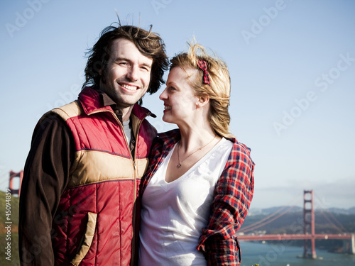 """USA, California, San Francisco, young couple standing, Golden Gate Bridge in background"""