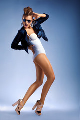 Young sexy fashion dancing woman isolated in sunglasses