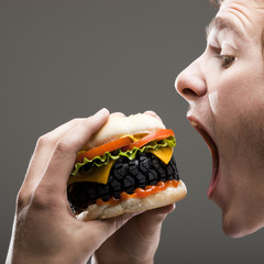 """Side view of young man about to bite a tire hamburger, close up"""