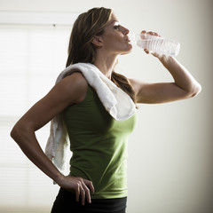 """USA, Utah, Orem, young woman drinking water after exercising"""