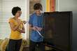 """USA, Utah, Provo, couple installing new TV set"""