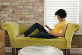 """USA, Utah, Provo, woman sitting on sofa and reading book"""