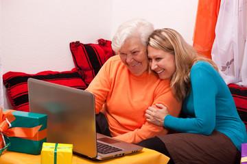 seniorin und junge frau sitzen an laptop und haben spass 2