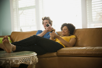 """USA, Utah, Provo, couple sitting on sofa watching TV"""