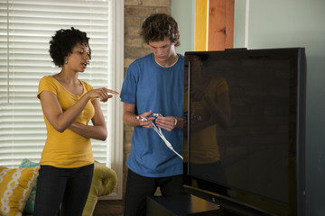 """USA, Utah, Provo, couple installing new TV set"""