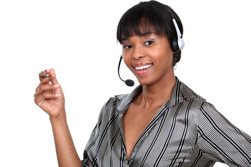 Woman wearing a telephone headset and holding a pen