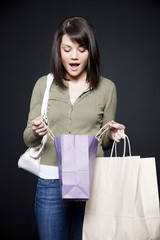 Studio portrait of young woman holding shopping bags
