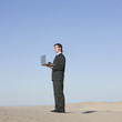 """USA, Utah, Little Sahara, businessman looking through telescope in desert"""