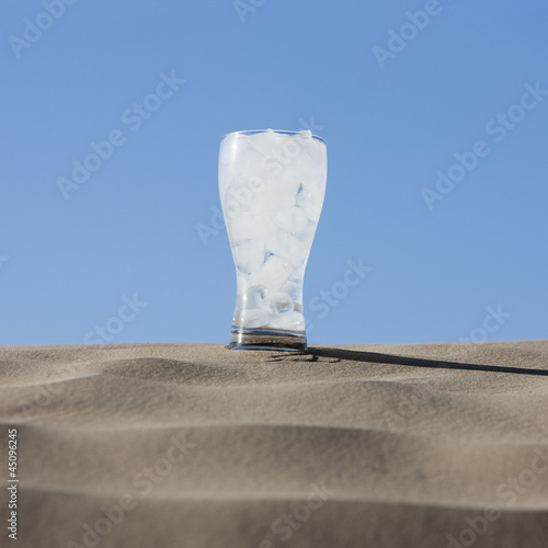 """USA, Utah, Little Sahara, glass of ice cold water in desert"""