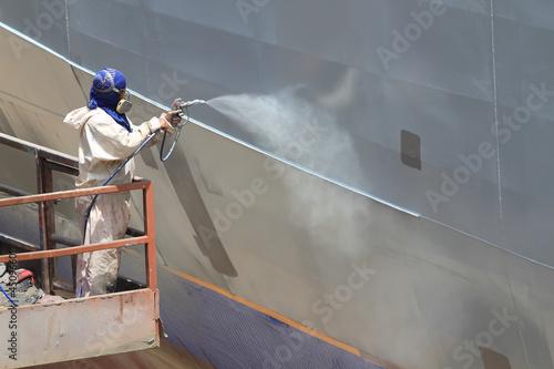 worker painting ship hull using airbrush gray paint