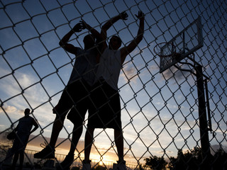 """USA, Utah, Salt Lake City, three young men playing street basketball, low angle view"""