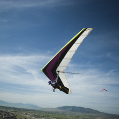 """USA, Utah, Lehi, mid adult man hang gliding, low angle view"""
