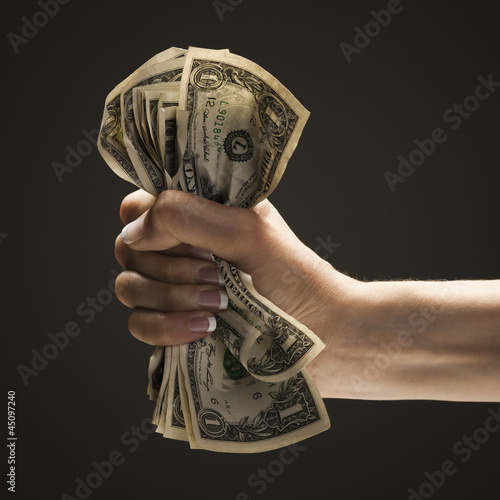 Young woman's hand holding a wad of US one dollar bills