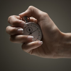 Young woman's hand holding stop clock