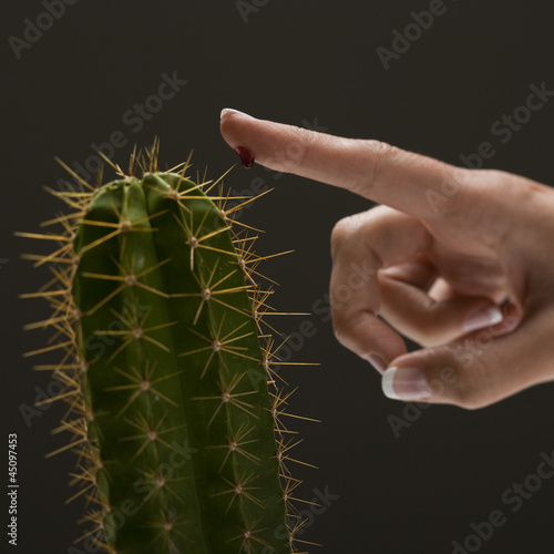 Young woman's hand touching cactus spike