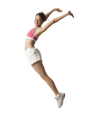 """Young woman jumping in the air, studio shot"""