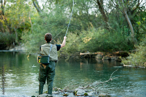 A fisherman fishing on a river