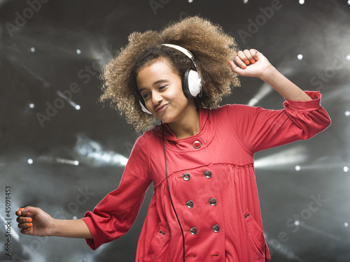 Girl (12-13) dancing with headphones