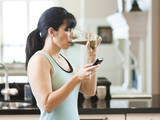 """USA, Utah, Alpine, mid adult woman drinking juice and using mobile phone in kitchen"""