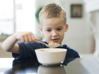 """USA, Utah, Alpine, boy (6-7) eating cereals by table"""