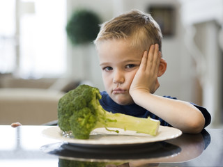"""USA, Utah, Alpine, boy (6-7) sulking by table with plate of broccoli"""