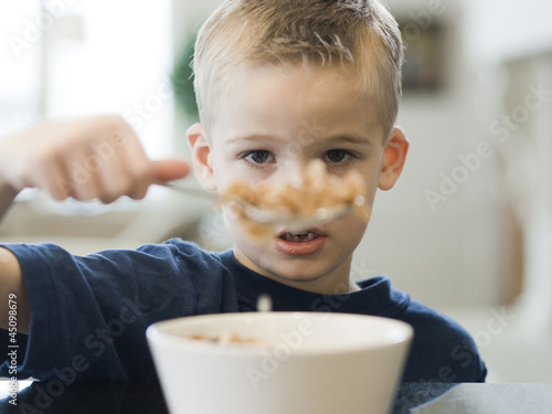 """USA, Utah, Alpine, boy (6-7) eating cereals by table, portrait"""